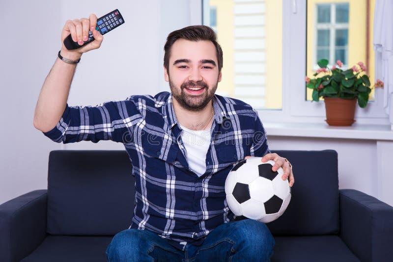 Gelukkige jonge mens het letten op voetbal op TV thuis stock afbeeldingen
