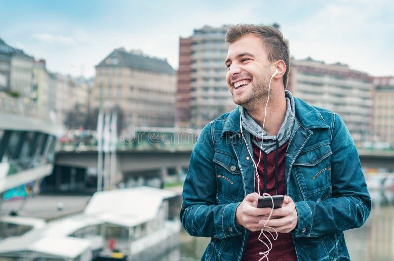 Gelukkige jonge mens het luisteren muziek die op straat genieten van stock foto's