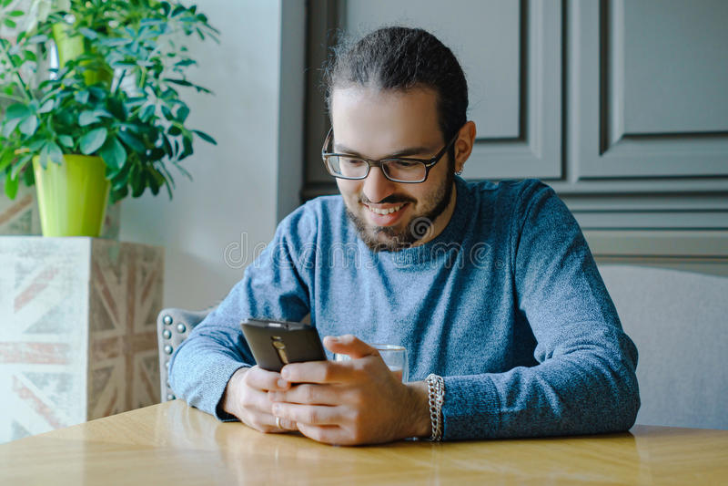 Gelukkige jonge mens in koffie met smartphone bedrijfsonderbreking stock foto's