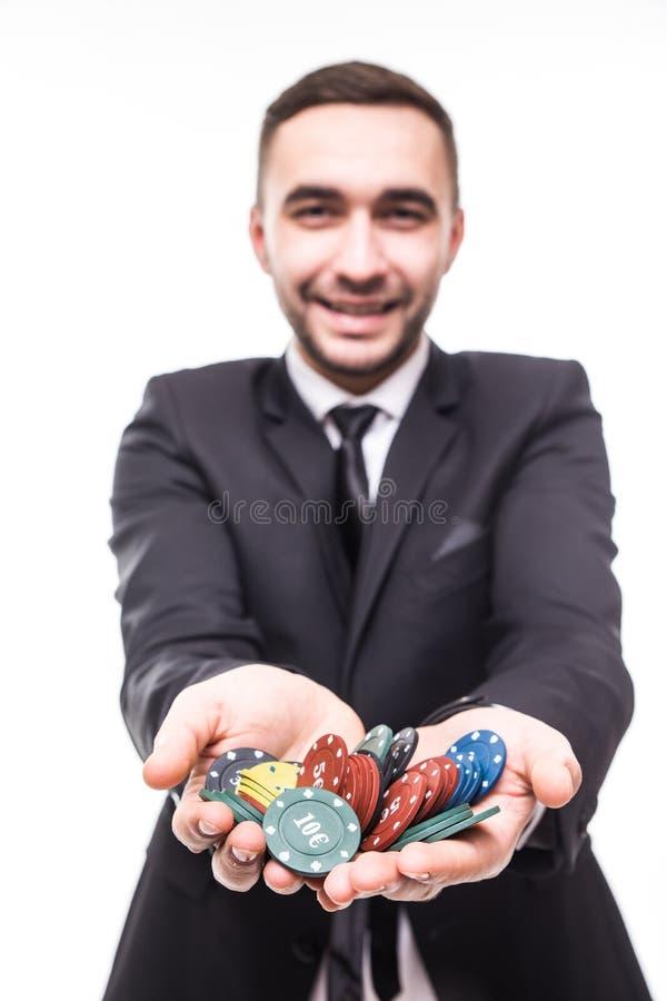 Gelukkige jonge mens in kostuum die de spaanders van de winstpook steunen bij spel royalty-vrije stock fotografie