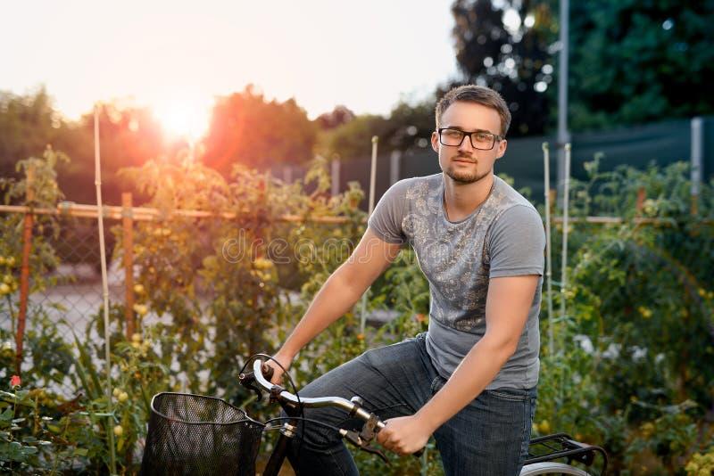 Gelukkige jonge mens met fiets in park Met glazen voor gezicht bij zonsondergang stock afbeeldingen
