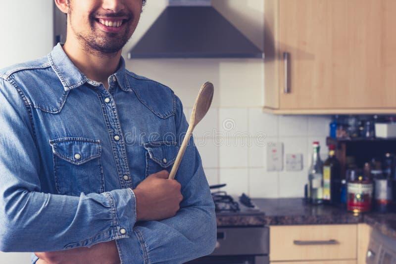 Gelukkige jonge mens met houten lepel in keuken stock afbeelding