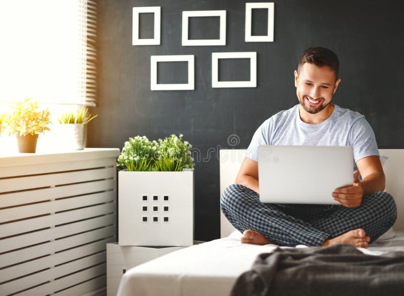 Gelukkige jonge mens met laptop in bed royalty-vrije stock foto's