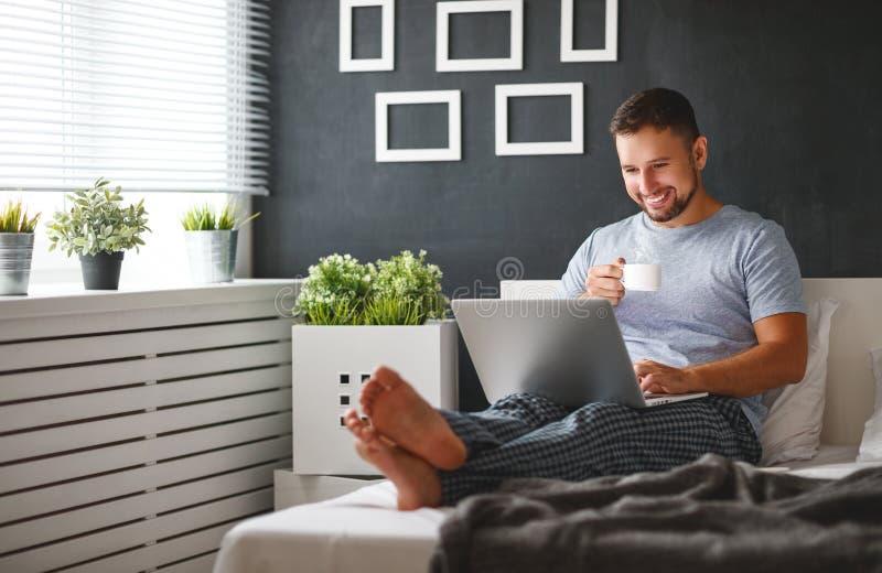 Gelukkige jonge mens met laptop en kop van koffie in bed stock foto