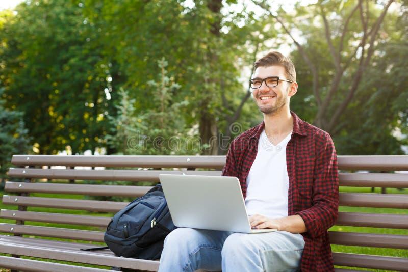 Gelukkige jonge mens met laptop in openlucht royalty-vrije stock foto's