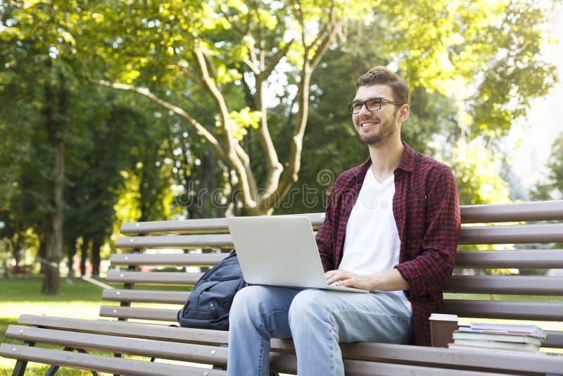 Gelukkige jonge mens met laptop in openlucht stock afbeeldingen