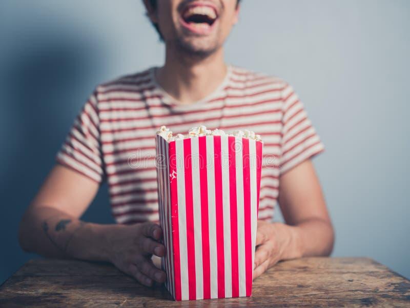 Gelukkige jonge mens met popcorn stock afbeelding