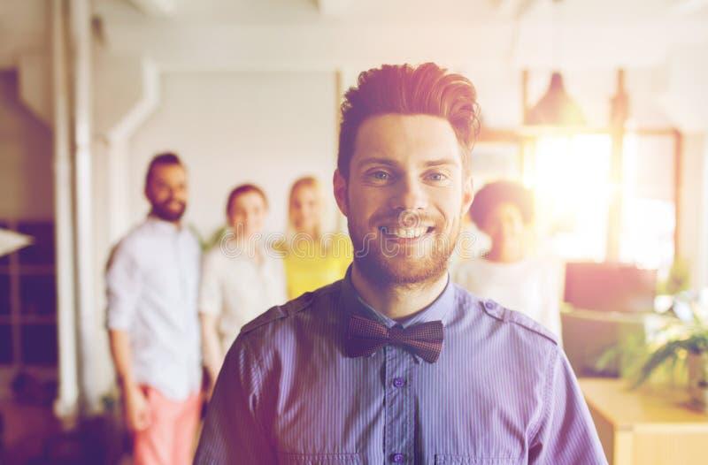 Gelukkige jonge mens over creatief team in bureau stock afbeeldingen