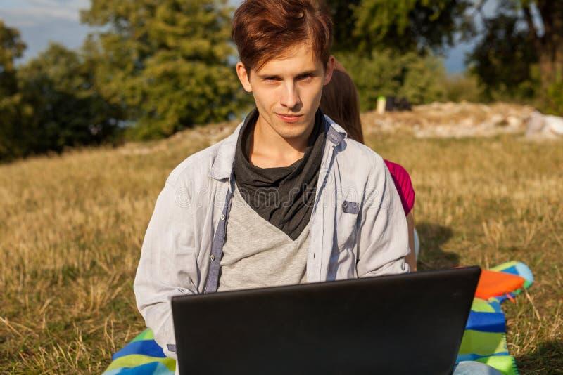 Gelukkige jonge mens in park het schrijven artikel op zijn laptop royalty-vrije stock fotografie