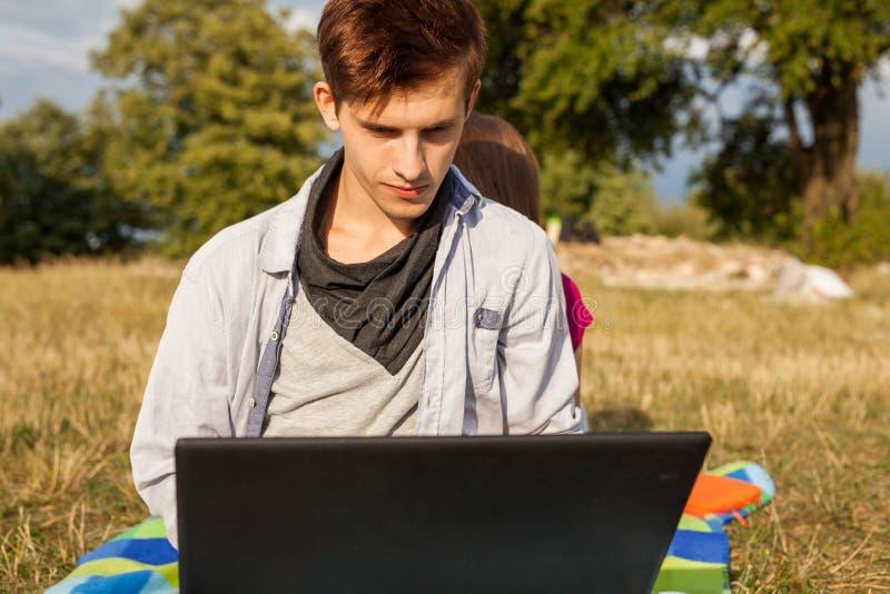 Gelukkige jonge mens in park het schrijven artikel op zijn laptop stock afbeelding