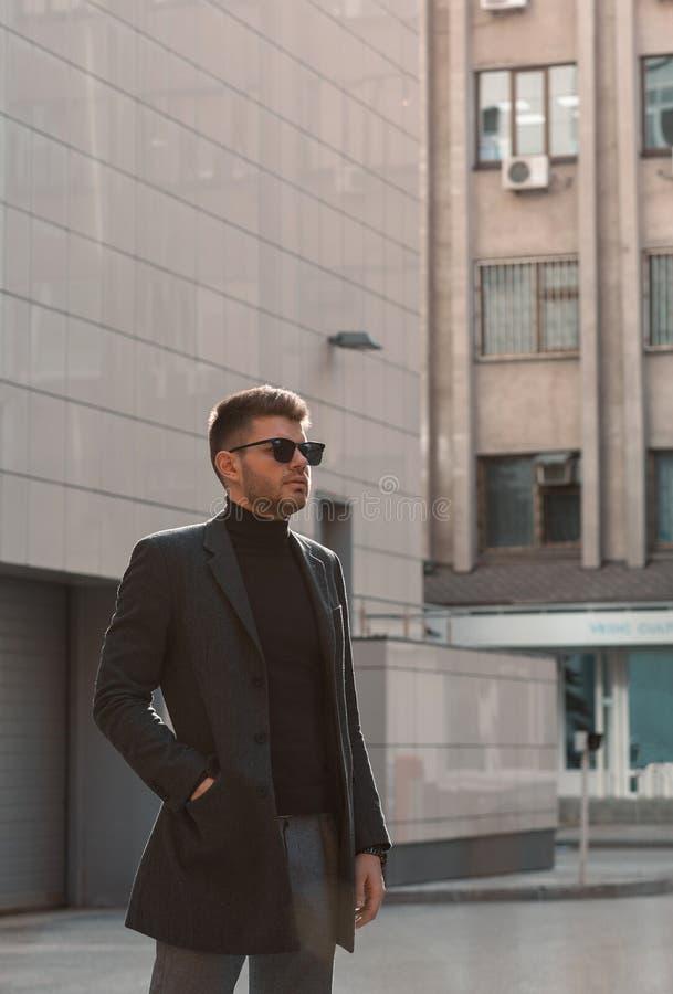 Gelukkige jonge mens in zwarte glazen en een grijze laag op de achtergrond van gebouwen stock fotografie