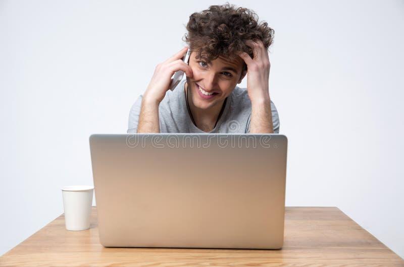 Gelukkige jonge mensenzitting bij de lijst met laptop stock foto's