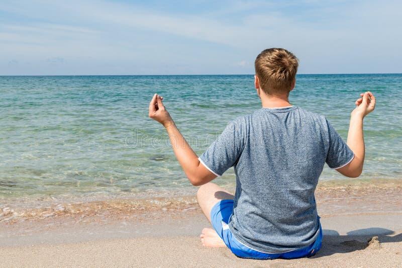 Gelukkige jonge mensenzitting met gekruiste benen op het strand Yoga en geschiktheid stock afbeelding