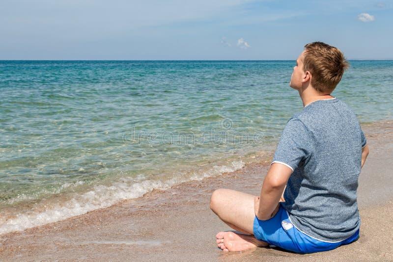 Gelukkige jonge mensenzitting met gekruiste benen op het strand Yoga en geschiktheid royalty-vrije stock foto's