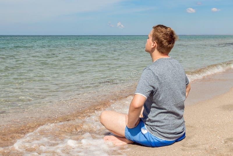 Gelukkige jonge mensenzitting met gekruiste benen op het strand Yoga en geschiktheid stock foto
