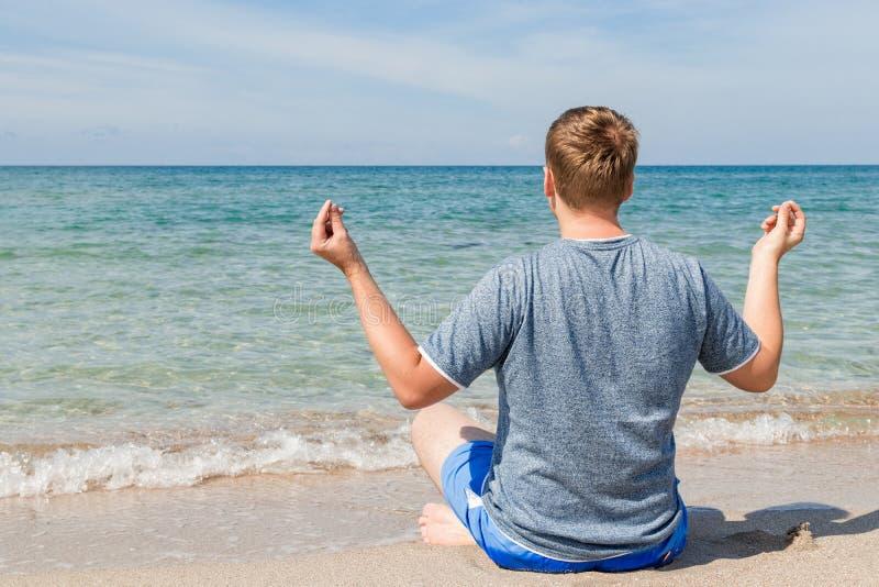 Gelukkige jonge mensenzitting met gekruiste benen op het strand Yoga en geschiktheid royalty-vrije stock foto