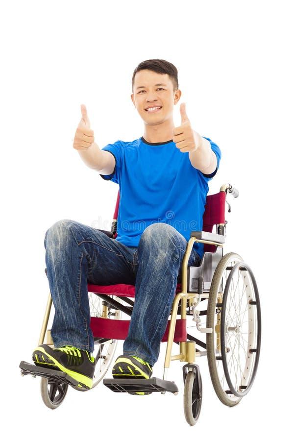 Gelukkige jonge mensenzitting op een rolstoel en een duim omhoog royalty-vrije stock foto's