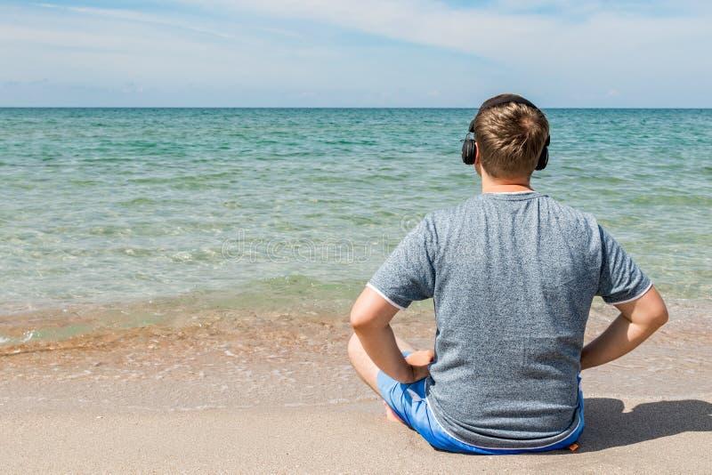 Gelukkige jonge mensenzitting op het strand die aan muziek op hoofdtelefoons luisteren De yoga en ontspant stock foto