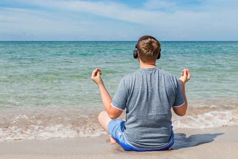 Gelukkige jonge mensenzitting op het strand die aan muziek op hoofdtelefoons luisteren De yoga en ontspant royalty-vrije stock afbeelding