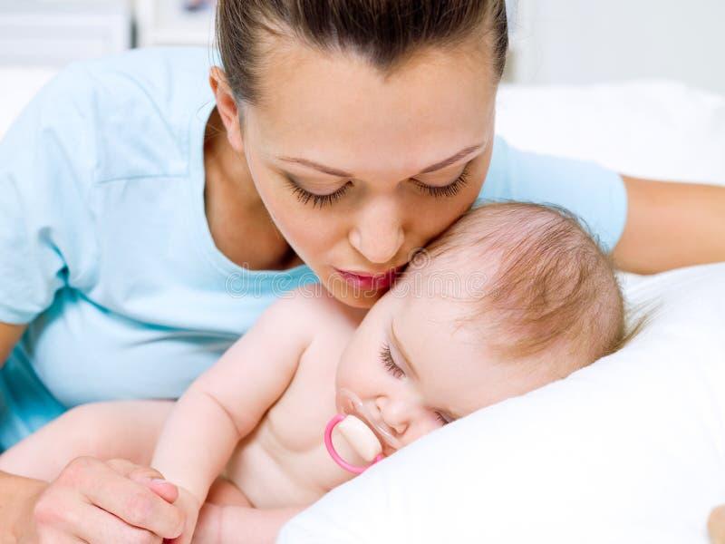 Gelukkige jonge moeder dichtbij pasgeboren slaap stock afbeeldingen