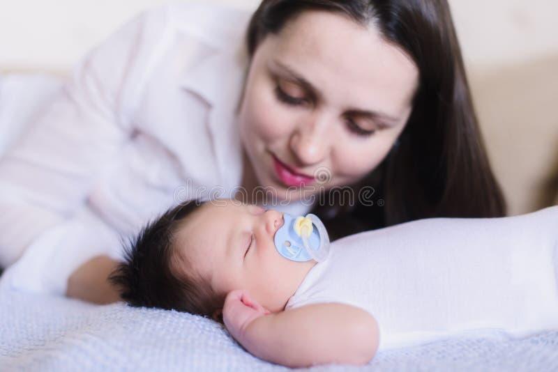 Gelukkige jonge moeder dichtbij slaapbaby Close-up royalty-vrije stock afbeelding