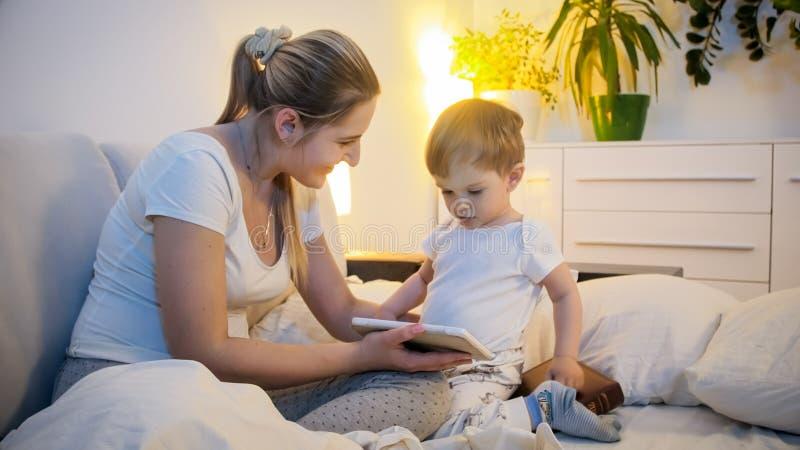 Gelukkige jonge moeder die beeldverhaal op digitale tablet tonen aan haar peuterzoon alvorens naar slaap te gaan stock foto