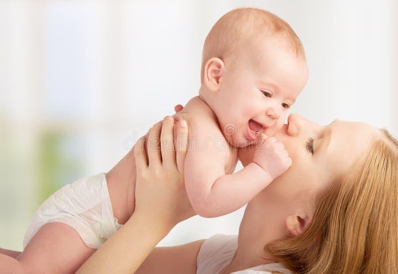 Gelukkige jonge moeder die een baby kussen stock foto