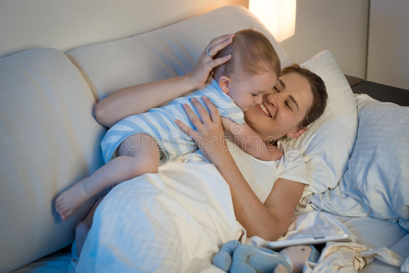 Gelukkige jonge moeder die en haar babyjongen in bed spelen omhelzen bij royalty-vrije stock afbeeldingen
