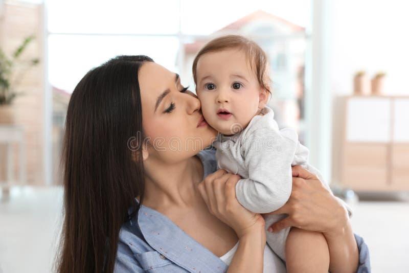 Gelukkige jonge moeder die haar aanbiddelijke baby kust royalty-vrije stock foto's