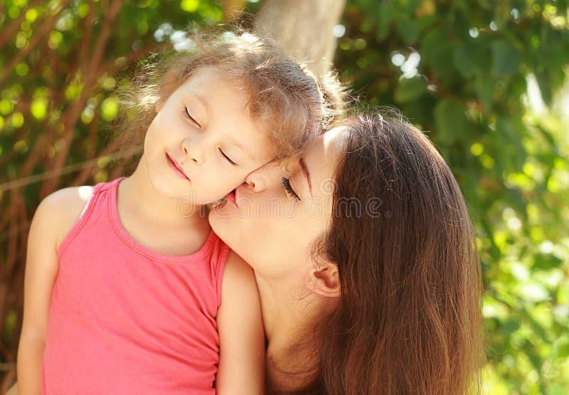 Gelukkige jonge moeder die haar gelukkig joying jong geitje kussen royalty-vrije stock fotografie