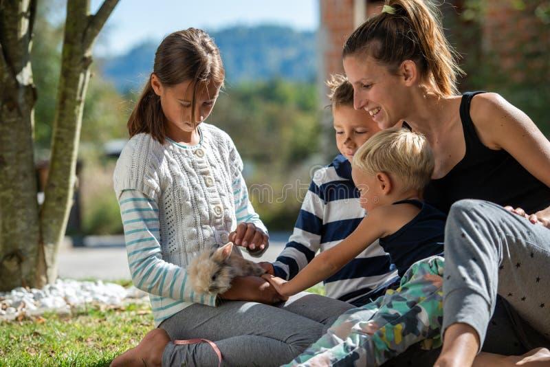 Gelukkige jonge moeder die met haar drie jonge geitjes van tijd genieten royalty-vrije stock afbeeldingen