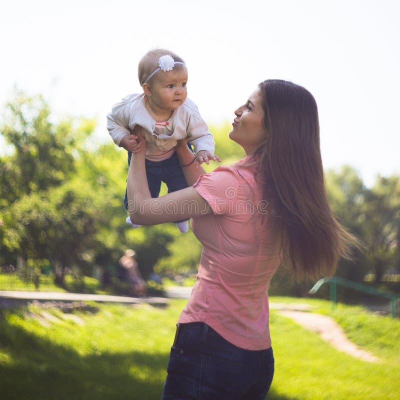 Gelukkige jonge moeder die met haar leuke baby bij de zomer zonnige dag lopen stock afbeelding