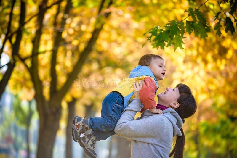 Gelukkige jonge moeder die zoete peuterjongen, familie houden die pret samen buiten op een aardige zonnige de herfstdag hebben Le royalty-vrije stock afbeelding