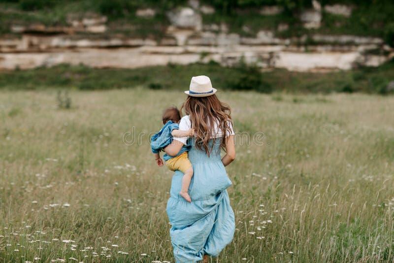 Gelukkige jonge moeder in een lange blauwe kleding die met haar zoon van de littltebaby op gebied met bloemen door de berg lopen stock foto's