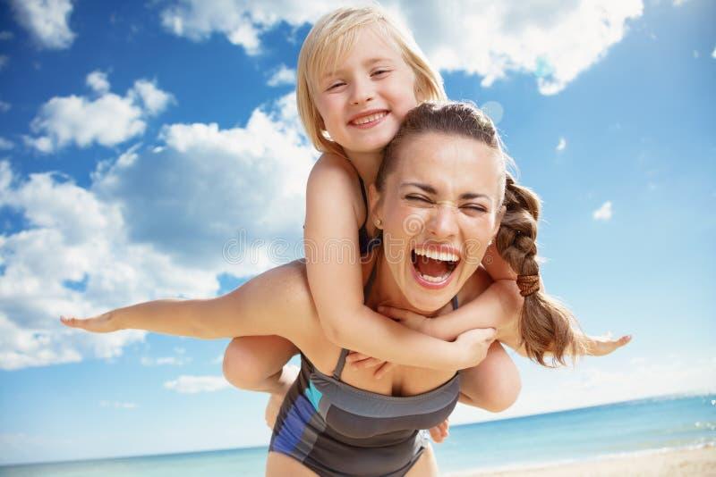 Gelukkige jonge moeder en dochter bij zich zeekust het verheugen stock afbeelding