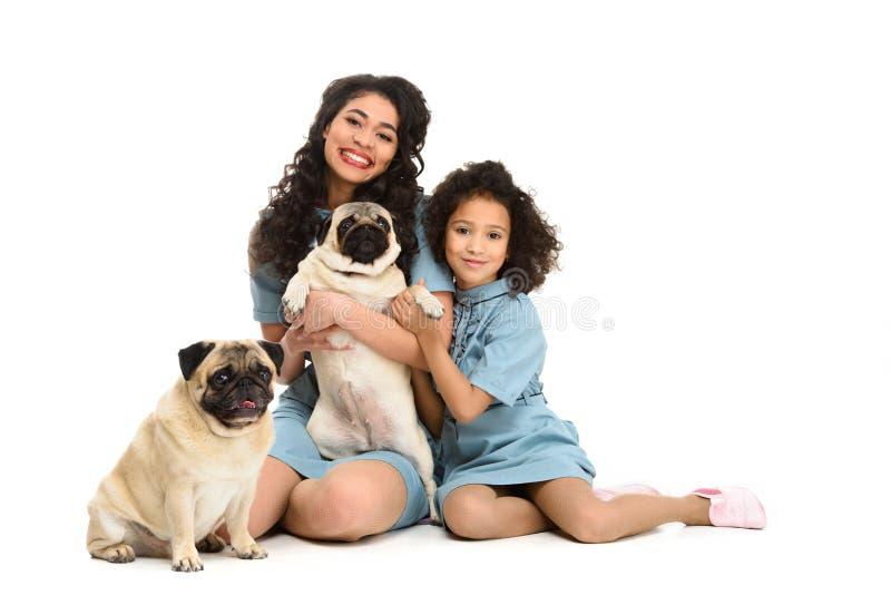 gelukkige jonge moeder en dochterzitting op vloer met twee aanbiddelijke pugs stock fotografie