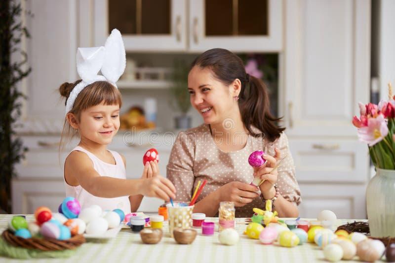 Gelukkige jonge moeder en haar twee kleine dochters met de oren van het witte konijn op hun hoofdenkleurstof de eieren voor de Pa royalty-vrije stock foto's