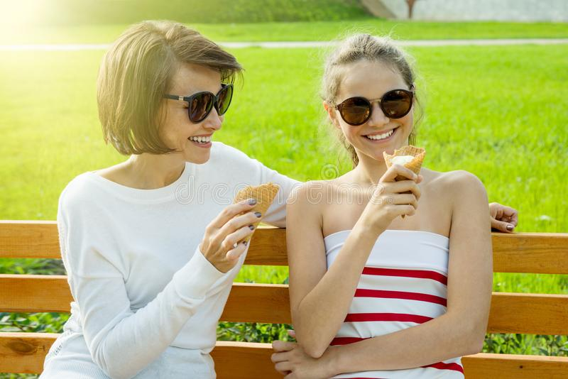 Gelukkige jonge moeder en leuke dochter van een tiener in een stadspark die roomijs, het spreken en het lachen eten royalty-vrije stock afbeeldingen