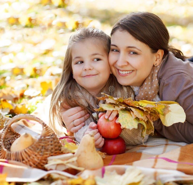 Gelukkige jonge moeder met dochter in de herfstpark stock afbeelding