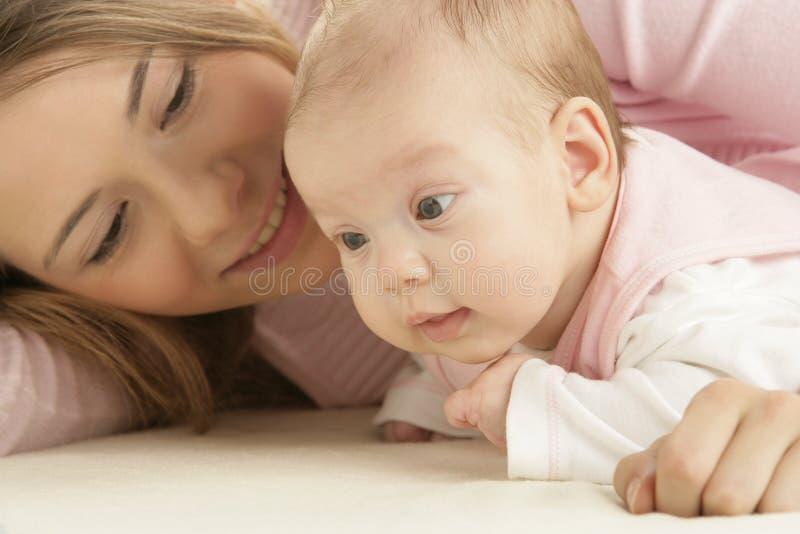 Gelukkige jonge moeder met haar pasgeboren baby royalty-vrije stock afbeelding