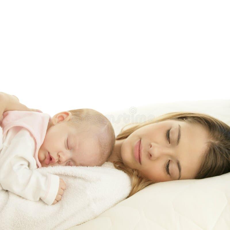 Gelukkige jonge moeder met haar slaap pasgeboren baby royalty-vrije stock afbeelding