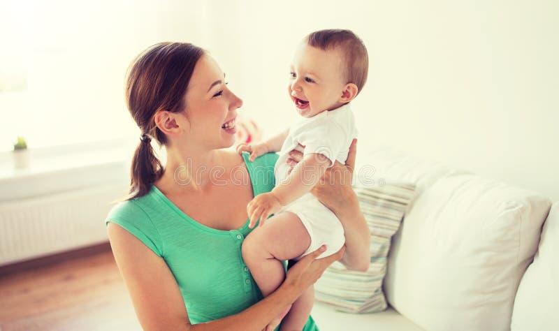 Gelukkige jonge moeder met weinig baby thuis royalty-vrije stock fotografie