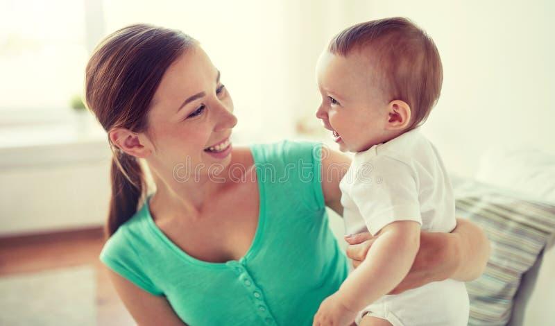 Gelukkige jonge moeder met weinig baby thuis royalty-vrije stock foto