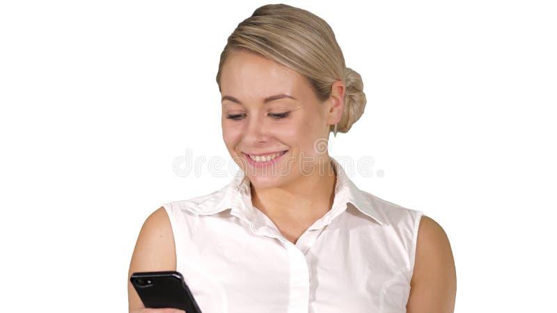 Gelukkige jonge mooie vrouw die en mobiele telefoon op witte achtergrond glimlachen met behulp van royalty-vrije stock afbeeldingen