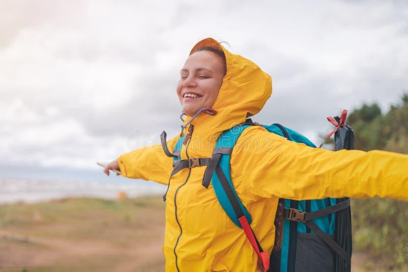 gelukkige jonge mooie vrouw in gele jasjewindjekker met een wandelingsrugzak op de kust van de Noordzee royalty-vrije stock afbeeldingen