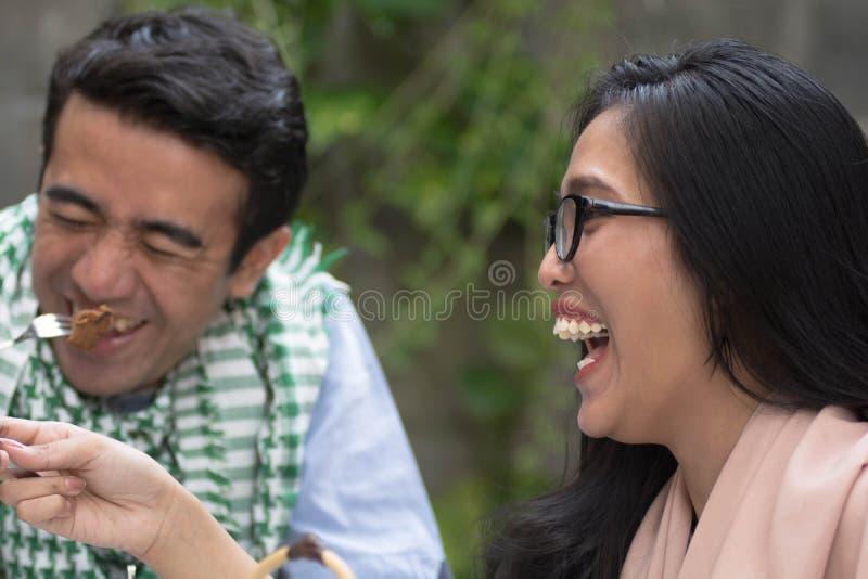 Gelukkige jonge moslim die en openlucht voedsel eten die lachen glimlachen stock fotografie