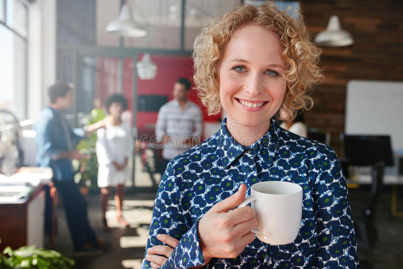 Gelukkige jonge onderneemster die koffie hebben stock foto's