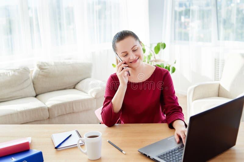 Gelukkige jonge onderneemsterzitting bij houten bureau die, die aan laptop werken en op mobiele telefoon met cliënt thuis bureau  royalty-vrije stock foto's