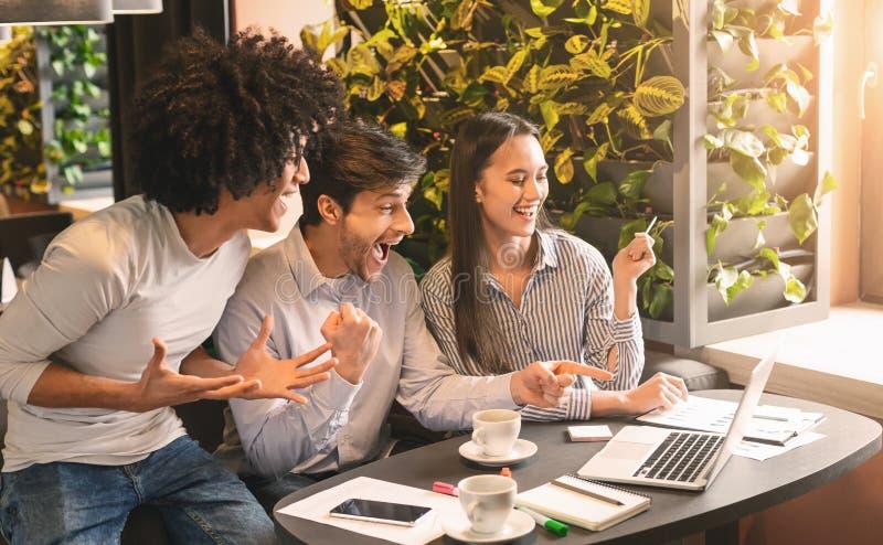 Gelukkige jonge ondernemers bij koffie het vieren succes samen royalty-vrije stock afbeelding