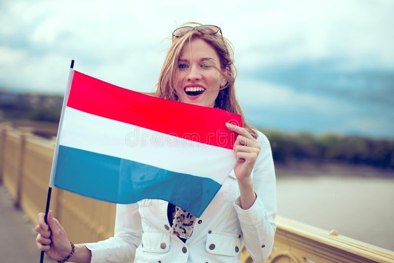 Gelukkige jonge opgewekte vrouw die Nederlandse vlag op brug houden stock afbeeldingen